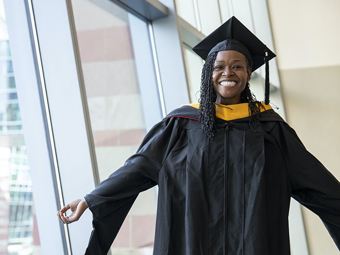 Graduate of University of Phoenix wearing her cap and gown while smiling